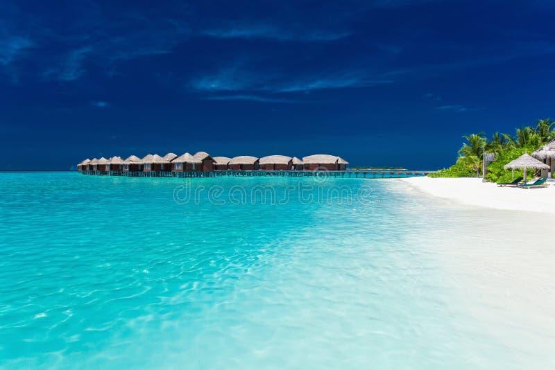 Bungallows d'Overwater dans la lagune bleue sur l'île tropicale image libre de droits