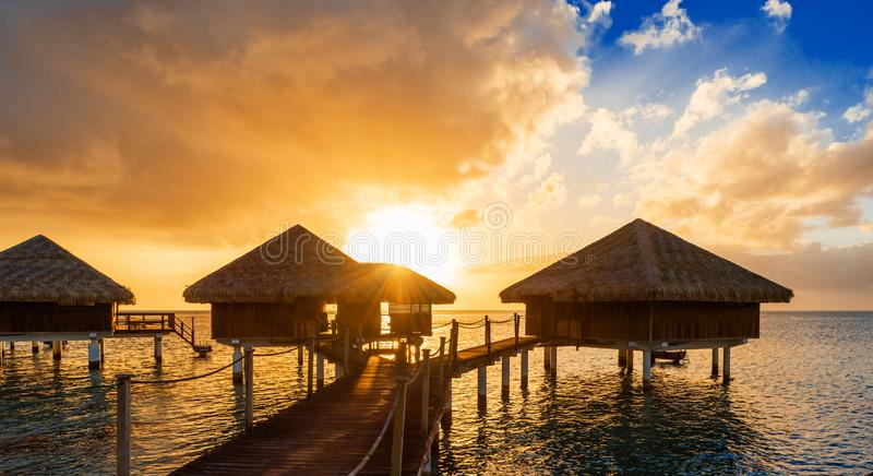 Bungalow al tramonto nella laguna Huahine, Polinesia francese immagine stock