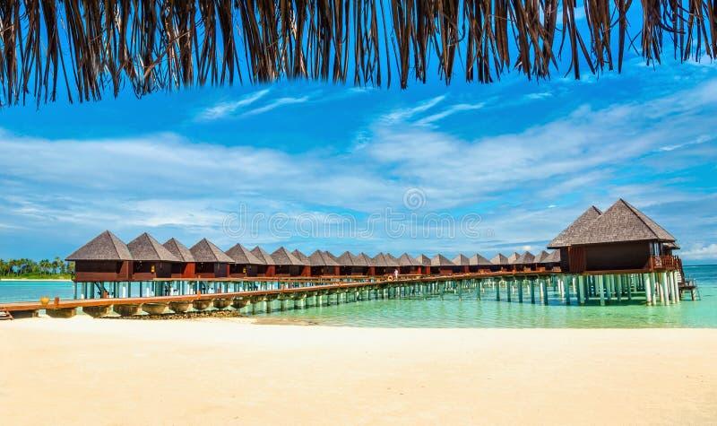 Bungalow di legno sui precedenti di acqua e di cielo blu azzurrati, Maldive immagine stock