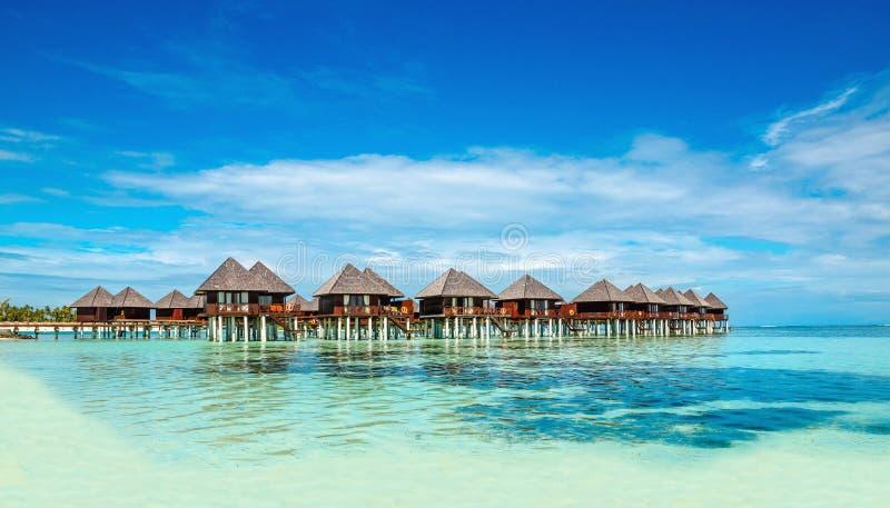Bungalow di legno sui precedenti di acqua e di cielo blu azzurrati, Maldive fotografia stock