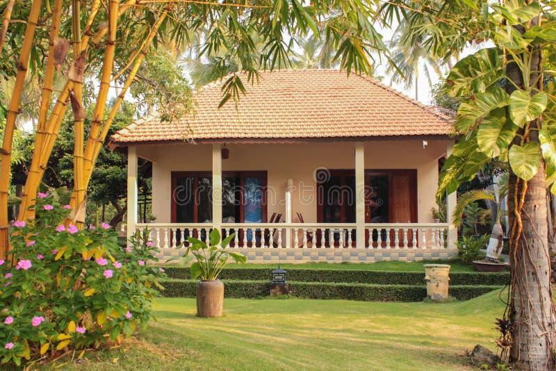 Bungalow e giardino - condominio in giardino tropicale - immagine stock