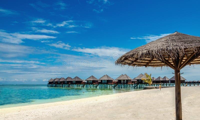 Bungalow ed ombrello di legno della palma sui precedenti di acqua e di cielo blu azzurrati, Maldive fotografia stock