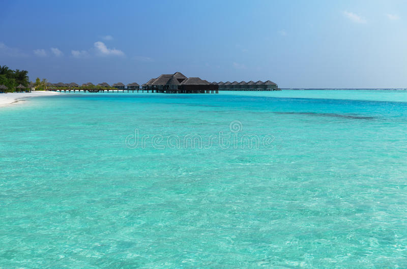 Bungalow huts in sea water on exotic resort beach. Travel, tourism, vacation and summer holidays concept - bungalow huts in sea water on exotic resort beach royalty free stock images