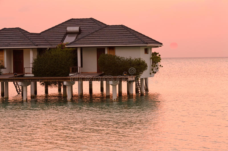 Bungalow in Ocean at Sunset, Maldives stock photo