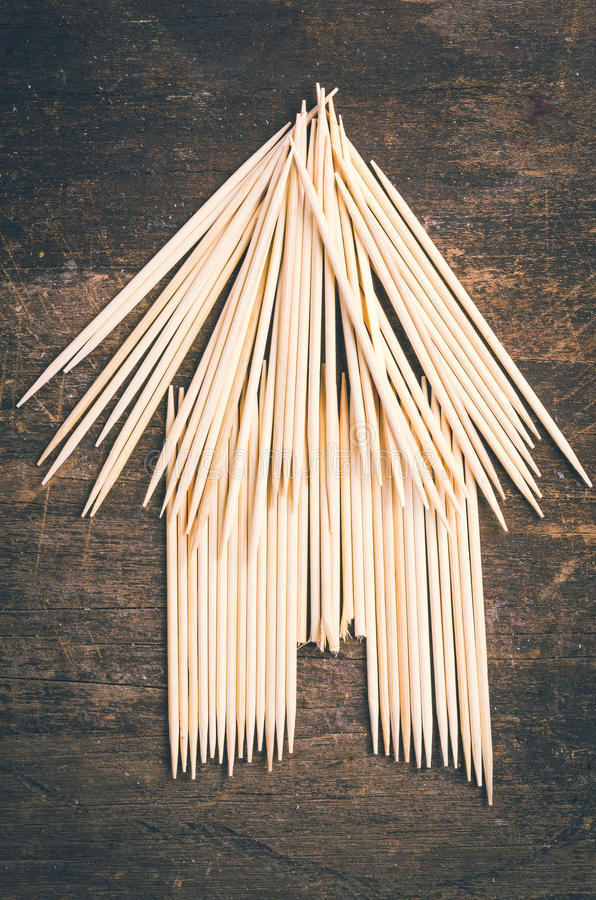 Bungalow simple hut type design from using. Toothpicks on dark wooden surface royalty free stock photos