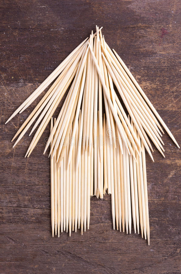 Bungalow simple hut type design from using. Toothpicks on dark wooden surface stock images