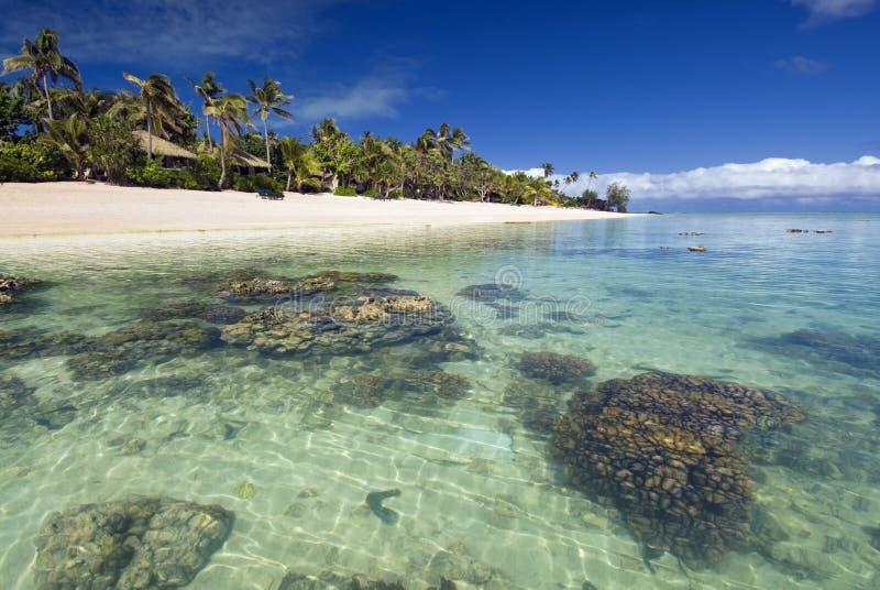 Bungalow sulla spiaggia tropicale, con la barriera corallina fotografie stock libere da diritti