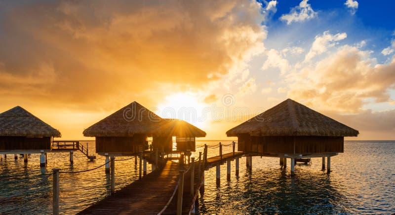 Bungalower på solnedgången i lagun Huahine, franska Polynesien fotografering för bildbyråer