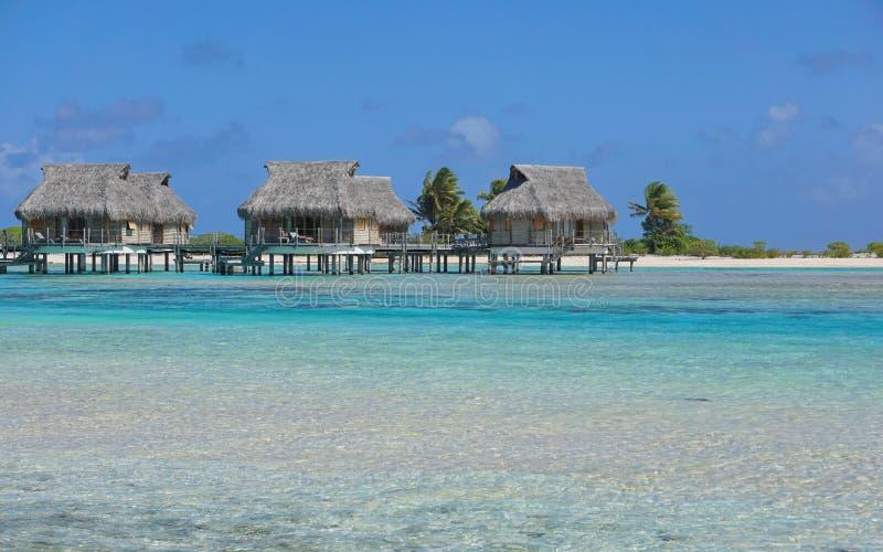 Bungalows tropicais sobre a água na lagoa foto de stock royalty free