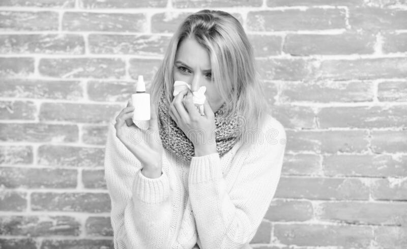 Bunged up nose. Cute woman nursing nasal cold or allergy. Pretty girl with runny nose holding nasal drops. Suffering royalty free stock photography
