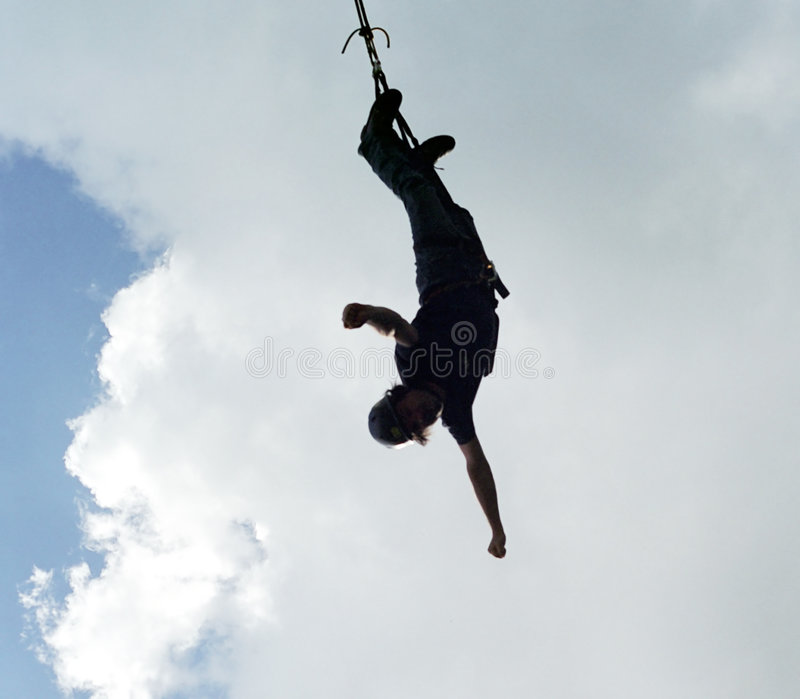 Bungee jumper. A silhouette of a bungee jumper stock photography