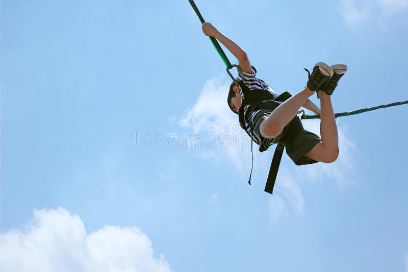 Bungee Jumping Boy Against Sky with Clipping Path. Happy 8 year old french-american boy bungee jumping against a blue and clouded sky with clipping path stock images