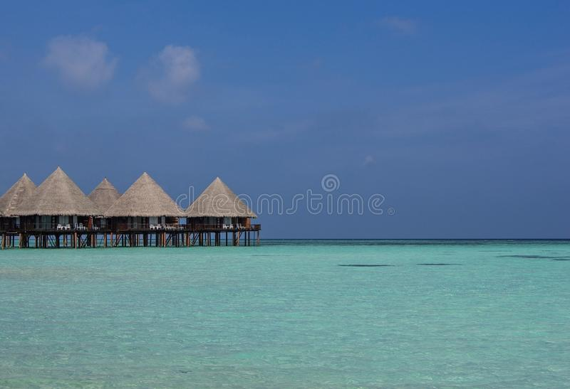 Bungelows on stilts over clear waters of Maldives stock images