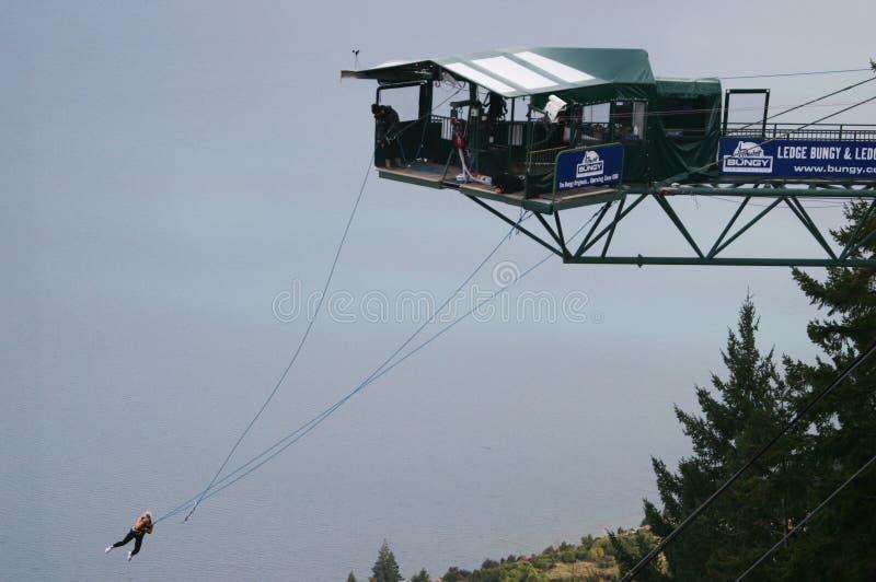 Bungy förkläde för fristil som dinglar från den hängande plattformen ovanför sjön arkivbild