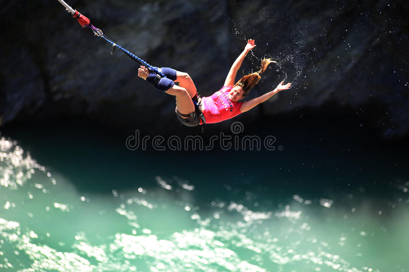 Bungy Jumping. Queenstown, New Zealand - January 11, 2011: A young woman jumping off the Kawarau bridge, plunging towards the Kawarau River in Queenstown, New