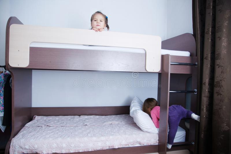 Bunk bed in child room.two little girl playing on bed. chocolate shade in the interior with white walls royalty free stock images