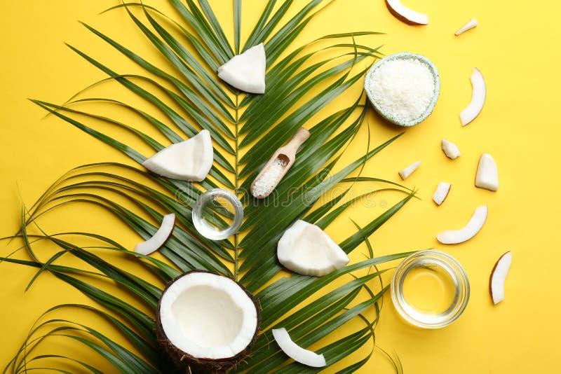 Bunkar av naturliga organiska olja och kokosnötter på gul bakgrund royaltyfri foto