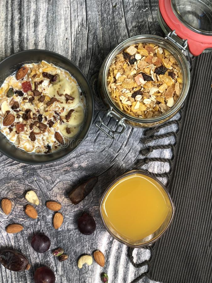 Bunkar för smoothies för havremyslisuperfoods som överträffas med bananen, havreflingor, mandel, granola med orange fruktsaft royaltyfri bild