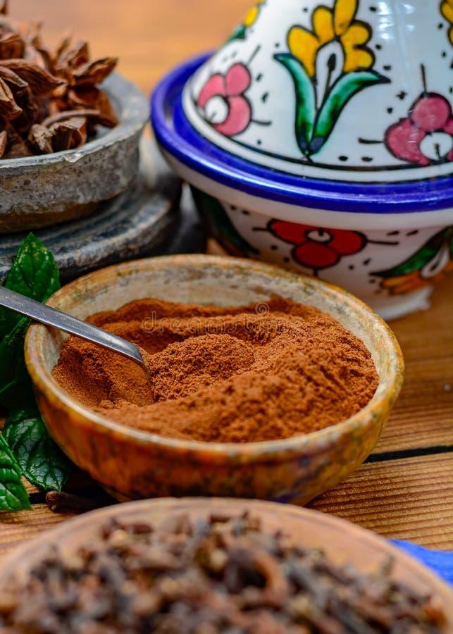 Bunkar med torkat kryddnejlikaknopp- och kryddnejlikapulver som används för att laga mat royaltyfria foton