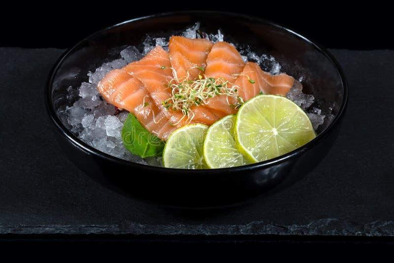 Bunke av den nya japanska sashimien av laxen med limefrukt på is royaltyfria bilder