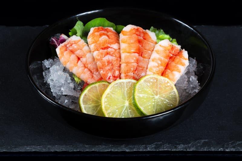 Bunke av den nya japanska sashimien av räkan med limefrukt på is arkivfoto