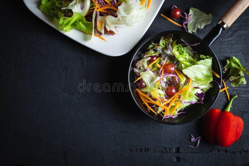 Bunke av grönsaksallad på svart bakgrund arkivfoton