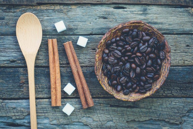 Bunke av grillade kaffebönor och en sked med kanelbruna pinnar arkivfoton