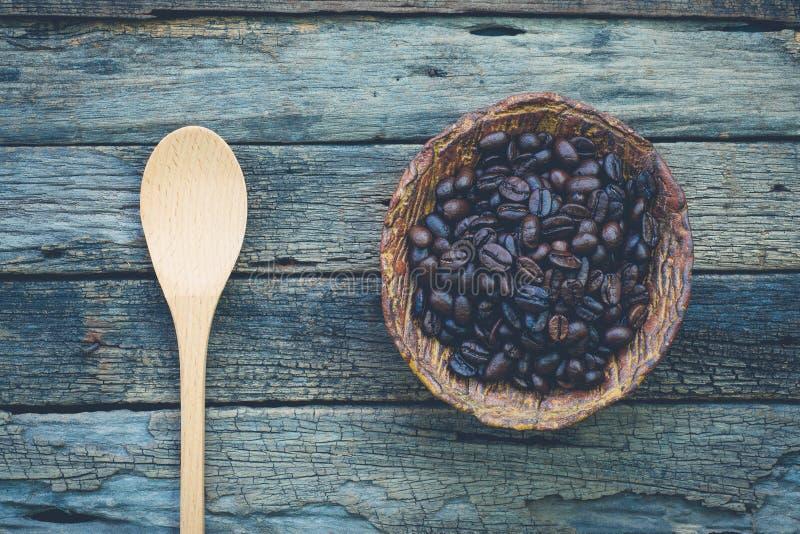 Bunke av grillade kaffebönor och en sked på mycket gammalt och lantligt arkivbilder