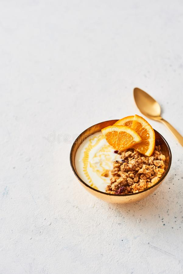 Bunke av hemlagad granola med yoghurt, honung och den nya apelsinen arkivfoto