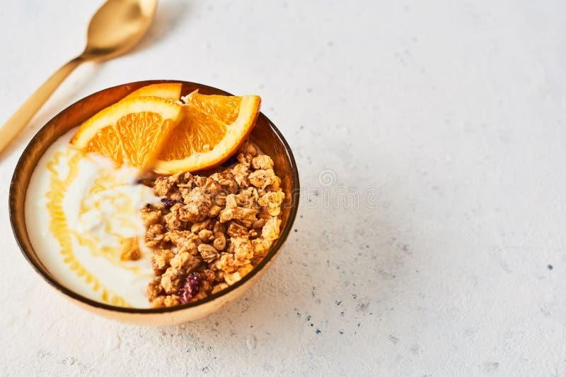 Bunke av hemlagad granola med yoghurt, honung och den nya apelsinen fotografering för bildbyråer
