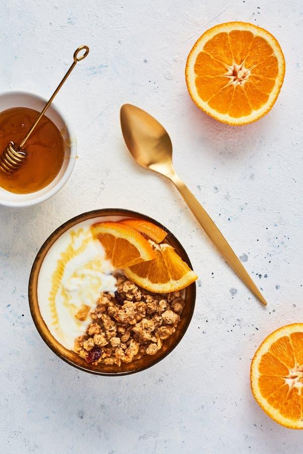Bunke av hemlagad granola med yoghurt, honung och den nya apelsinen arkivbild