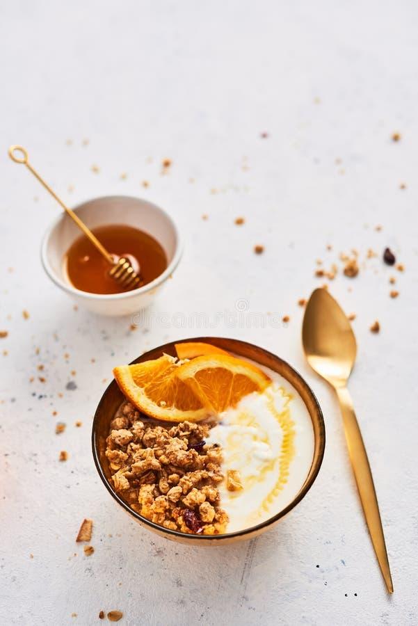 Bunke av hemlagad granola med yoghurt, honung och den nya apelsinen royaltyfria foton
