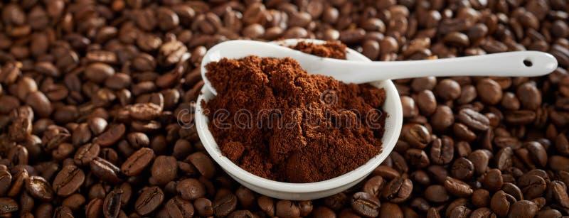 Bunke av jordkaffe över grillade kaffebönor arkivfoto