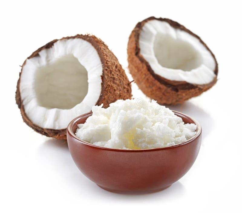 Bunke av kokosnötolja och nya kokosnötter arkivbilder