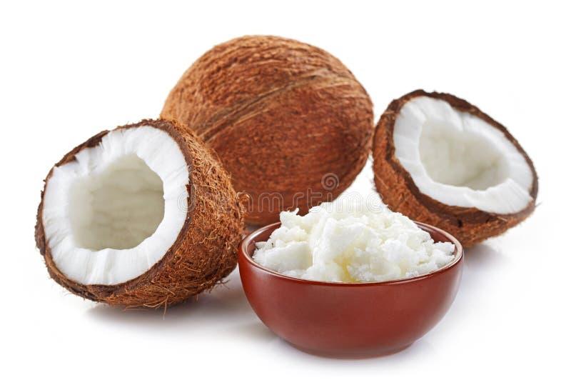 Bunke av kokosnötolja och nya kokosnötter royaltyfri foto