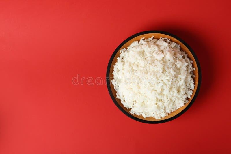 Bunke av kokta ris på färgbakgrund, bästa sikt arkivfoto
