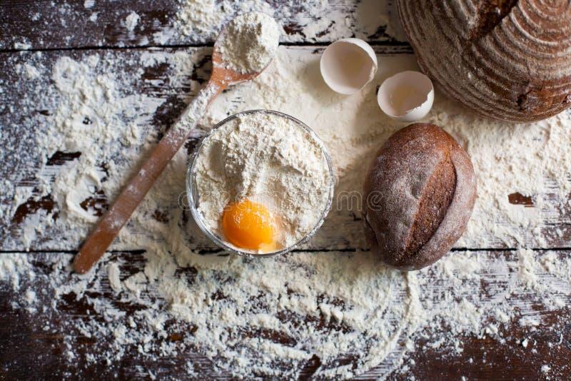 Bunke av mjöl med ägget och bröd fotografering för bildbyråer