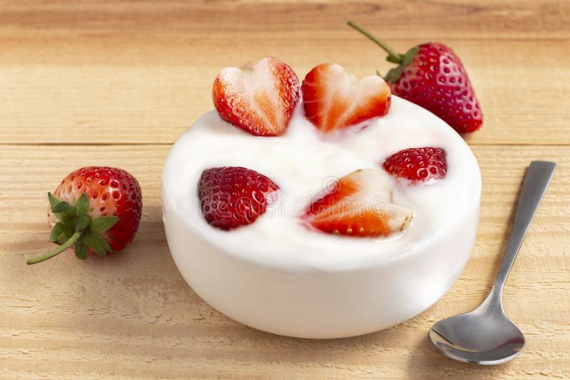 Bunke av yoghurt och röd fruktjordgubbe på trätabellen Yoghurten som göras från, mjölkar jäst av ökade bakterier som sötas ofta o royaltyfria foton