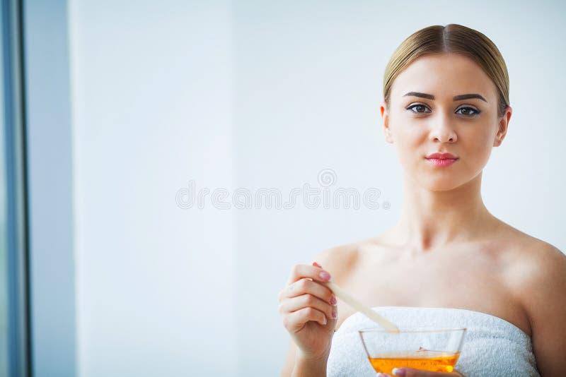 Bunke för paraffin för kvinnahåll orange Kvinna i skönhetsalong arkivbild