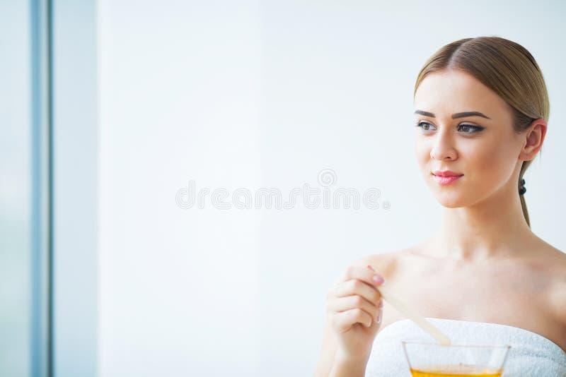 Bunke för paraffin för kvinnahåll orange Kvinna i skönhetsalong royaltyfria foton