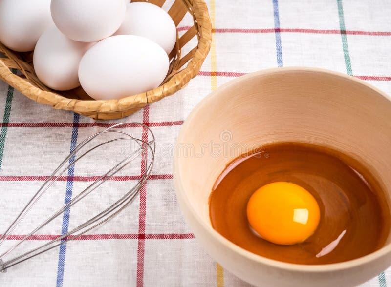 Bunke med äggula, en träkorg med ägg och en korg för att slå på tabellen royaltyfria bilder
