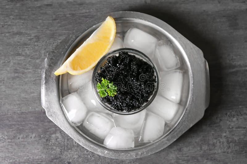 Bunke med den läckra svarta kaviaren och is-kuber på grå bakgrund royaltyfri fotografi