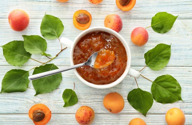 Bunke med driftstopp och nya aprikors på trätabellen arkivfoton