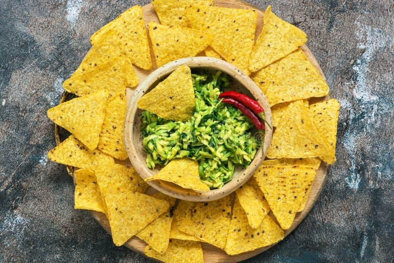Bunke med guacamole med nachos på en lantlig bakgrund Traditionellt mexicanskt mellanmål Bästa sikt, lekmanna- lägenhet royaltyfri foto