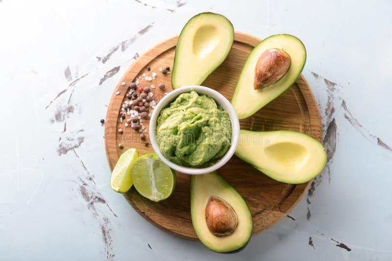 Bunke med läcker guacamole, kryddor och mogna avokadon på träbräde arkivfoton