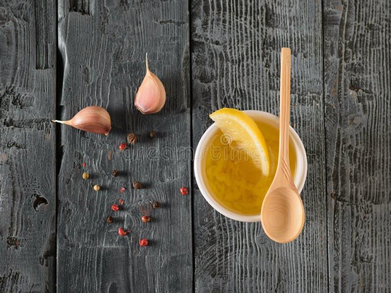 Bunke med olivolja, vitlök, peppar och citronen på en mörk trätabell Dressingen för bantar sallad övre sikt royaltyfri fotografi