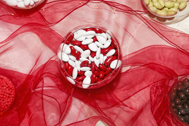 Bunke med röda och vita sockrade mandlar på en partitabell med silke arkivfoto