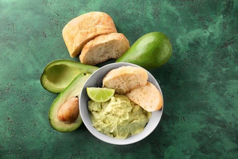 Bunke med smaklig guacamole, mogna avokadon och bröd på tabellen royaltyfri fotografi