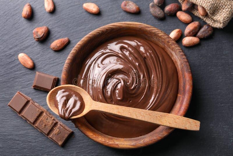 Bunke och sked med smaklig smältt choklad på tabellen arkivfoto