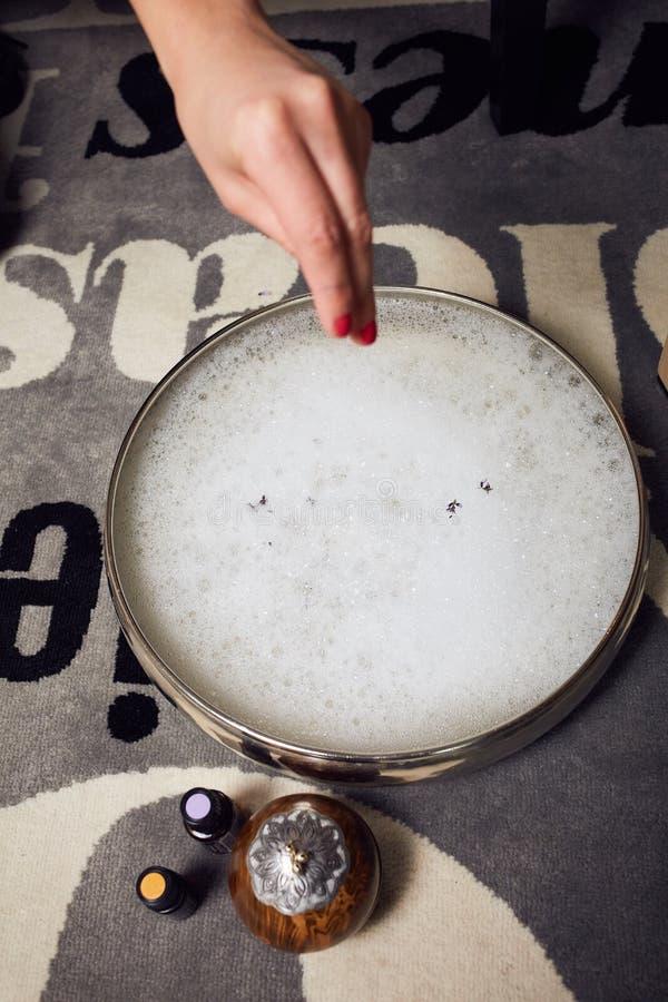 Bunke som fylls med ett bad av nödvändiga oljor som strilas med lavendelblommor royaltyfria bilder